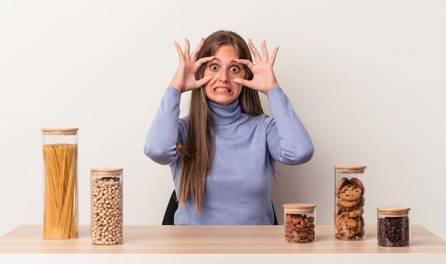 Jovem mulher caucasiana, sentada à mesa com o pote de comida, isolado no fundo branco, mantendo os olhos abertos para encontrar uma oportunidade de sucesso.