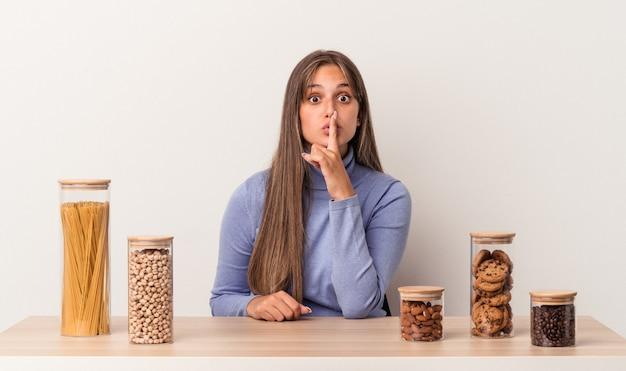 Jovem mulher caucasiana, sentada à mesa com o pote de comida, isolado no fundo branco, mantendo um segredo ou pedindo silêncio.