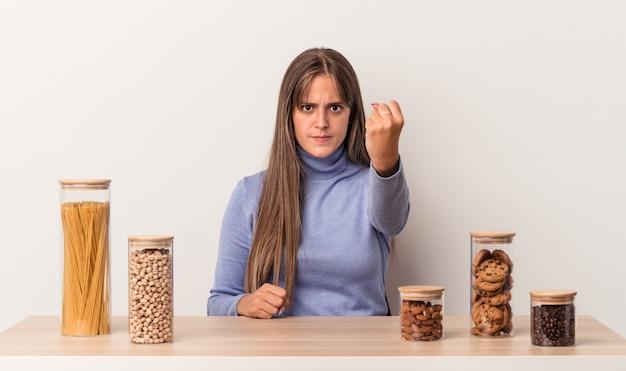 Jovem mulher caucasiana, sentada à mesa com o pote de comida, isolado no fundo branco, mostrando o punho para a câmera, expressão facial agressiva.