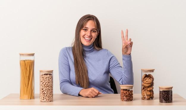 Jovem mulher caucasiana, sentada à mesa com o pote de comida isolado no fundo branco, mostrando sinal de vitória e sorrindo amplamente.