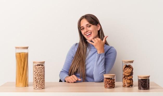 Jovem mulher caucasiana sentada à mesa com o pote de comida isolado no fundo branco, mostrando um gesto de chamada de telefone móvel com os dedos.