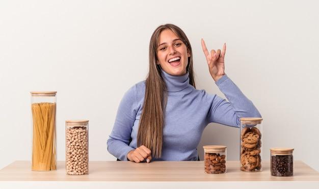 Jovem mulher caucasiana, sentada à mesa com o pote de comida, isolado no fundo branco, mostrando um gesto de chifres como um conceito de revolução.
