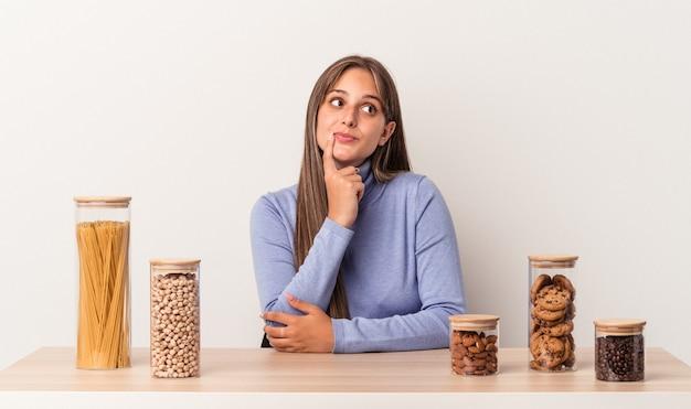 Jovem mulher caucasiana, sentada à mesa com o pote de comida, isolado no fundo branco, olhando de soslaio com expressão duvidosa e cética.