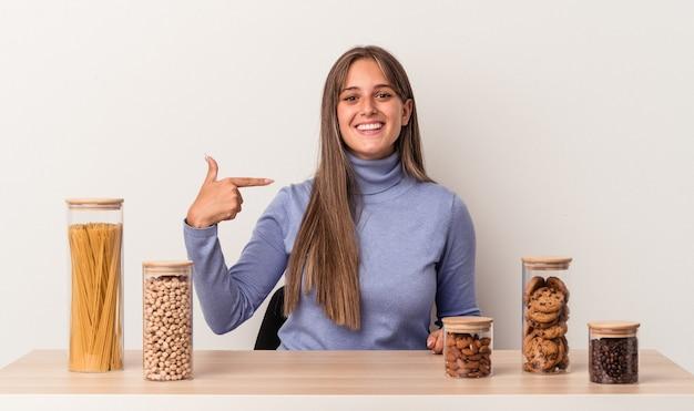 Jovem mulher caucasiana sentada à mesa com o pote de comida isolado no fundo branco pessoa apontando com a mão para um espaço de cópia de camisa, orgulhosa e confiante
