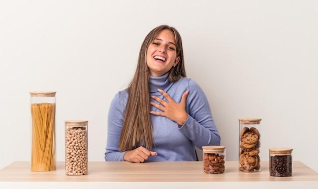 Jovem mulher caucasiana, sentada à mesa com o pote de comida, isolado no fundo branco, ri alto, mantendo a mão no peito.