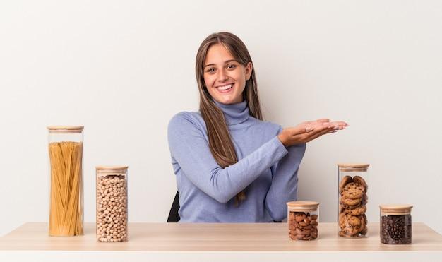 Jovem mulher caucasiana, sentada à mesa com o pote de comida, isolado no fundo branco, segurando um espaço de cópia na palma da mão.
