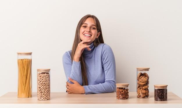Jovem mulher caucasiana, sentada à mesa com o pote de comida, isolado no fundo branco, sorrindo feliz e confiante, tocando o queixo com a mão.