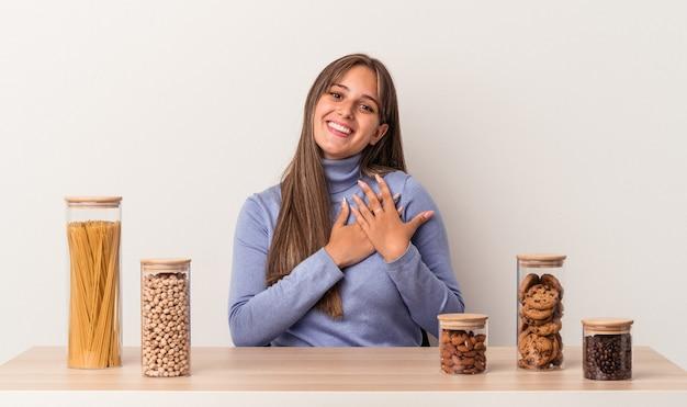 Jovem mulher caucasiana sentada à mesa com o pote de comida isolado no fundo branco tem uma expressão amigável, pressionando a palma da mão no peito. conceito de amor.