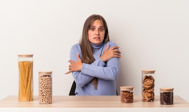 Jovem mulher caucasiana, sentada à mesa com um pote de comida, isolado no fundo branco, ficando frio devido à baixa temperatura ou a uma doença.