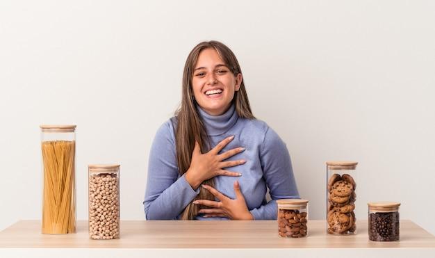 Jovem mulher caucasiana, sentada à mesa com um pote de comida isolado no fundo branco, ri alegremente e se diverte mantendo as mãos na barriga.