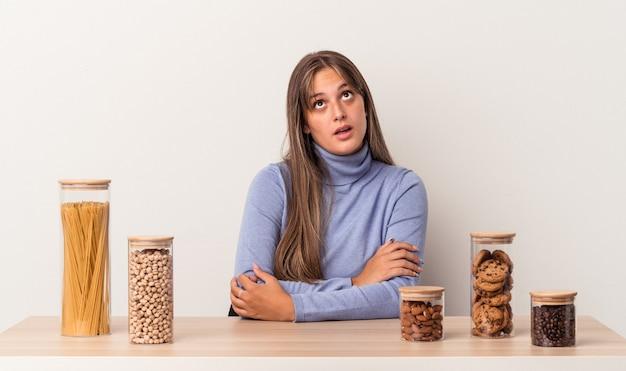 Jovem mulher caucasiana, sentada à mesa com uma panela de comida isolada no fundo branco, cansada de uma tarefa repetitiva.