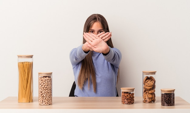 Jovem mulher caucasiana sentada à mesa com uma panela de comida isolada no fundo branco fazendo um gesto de negação