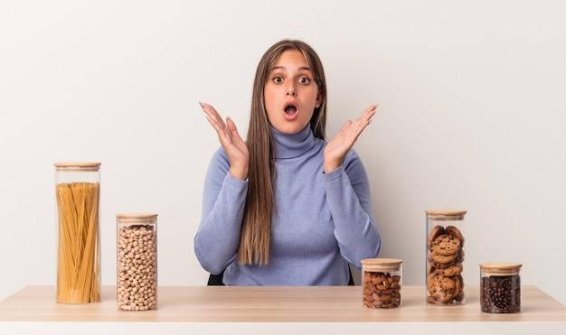 Jovem mulher caucasiana, sentada à mesa com uma panela de comida isolada no fundo branco, surpresa e chocada.
