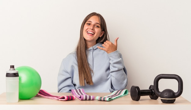 Jovem mulher caucasiana, sentada a uma mesa com equipamentos esportivos, isolados no fundo branco, mostrando um gesto de chamada de telefone móvel com os dedos.