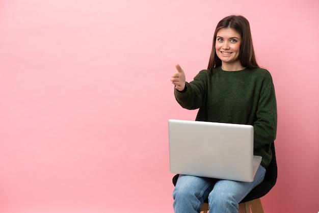 Jovem mulher caucasiana sentada em uma cadeira com seu laptop isolado em um fundo rosa apertando as mãos para fechar um bom negócio