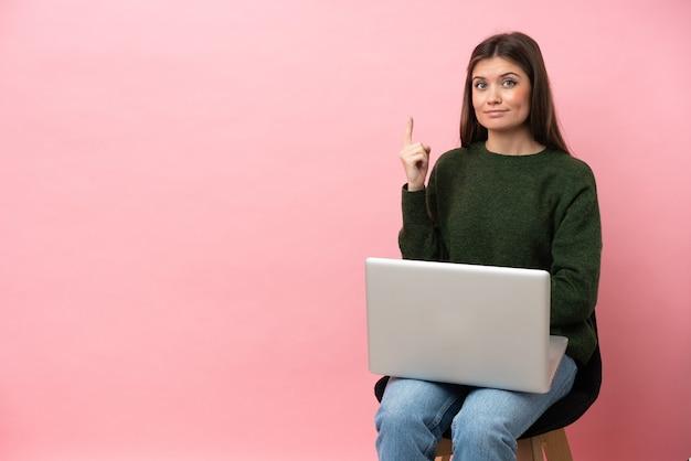 Jovem mulher caucasiana sentada em uma cadeira com seu laptop isolado em um fundo rosa apontando com o dedo indicador uma ótima ideia