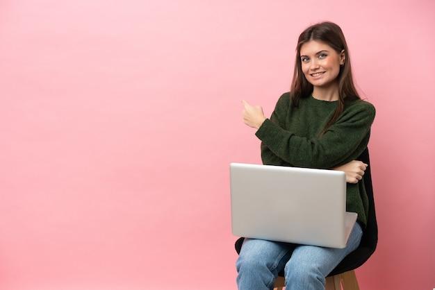 Jovem mulher caucasiana sentada em uma cadeira com seu laptop isolado em um fundo rosa apontando para trás