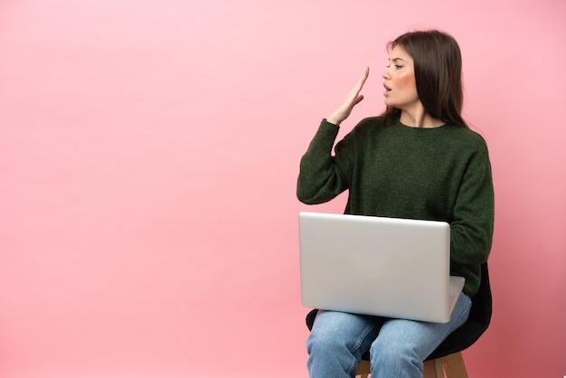 Jovem mulher caucasiana sentada em uma cadeira com seu laptop isolado em um fundo rosa, bocejando e cobrindo a boca aberta com a mão
