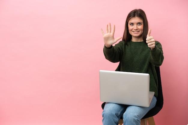 Jovem mulher caucasiana sentada em uma cadeira com seu laptop isolado em um fundo rosa, contando seis com os dedos