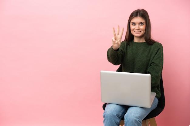 Jovem mulher caucasiana sentada em uma cadeira com seu laptop isolado em um fundo rosa feliz e contando três com os dedos