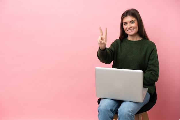 Jovem mulher caucasiana sentada em uma cadeira com seu laptop isolado em um fundo rosa, sorrindo e mostrando sinal de vitória
