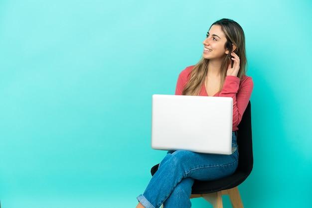 Jovem mulher caucasiana sentada em uma cadeira com seu pc isolado na parede azul, pensando uma ideia