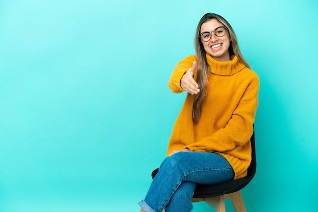 Jovem mulher caucasiana sentada em uma cadeira isolada em um fundo azul apertando as mãos para fechar um bom negócio