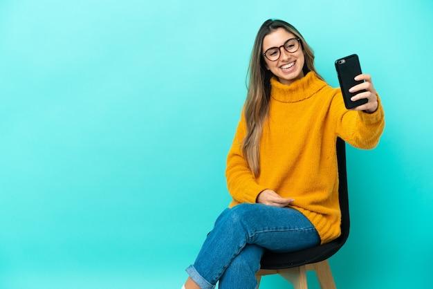 Jovem mulher caucasiana sentada em uma cadeira isolada em um fundo azul fazendo uma selfie