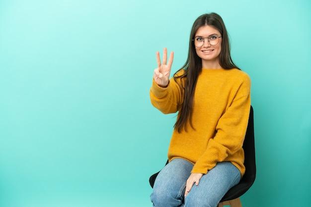 Jovem mulher caucasiana sentada em uma cadeira isolada em um fundo azul feliz e contando três com os dedos
