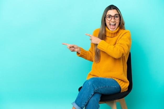 Jovem mulher caucasiana sentada em uma cadeira isolada em um fundo azul surpresa e apontando para o lado