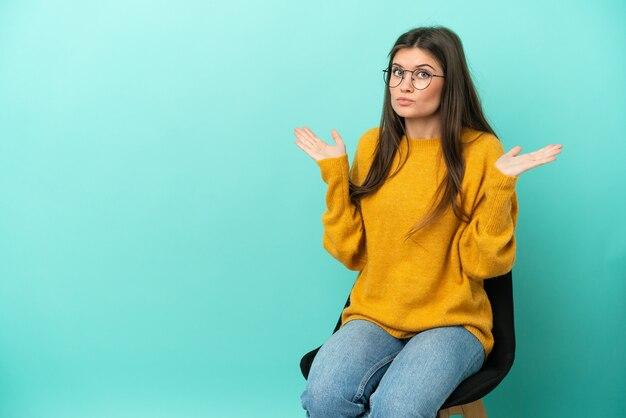 Jovem mulher caucasiana, sentada em uma cadeira isolada em um fundo azul, tendo dúvidas ao levantar as mãos