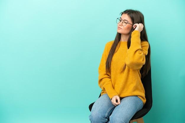 Jovem mulher caucasiana sentada em uma cadeira isolada em um fundo azul, tendo dúvidas e com expressão facial confusa