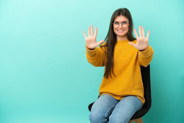 Jovem mulher caucasiana sentada em uma cadeira isolada no fundo azul, contando dez com os dedos
