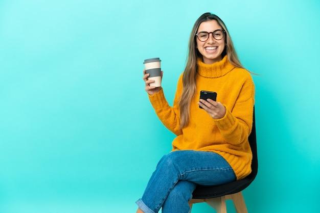 Jovem mulher caucasiana, sentada em uma cadeira isolada sobre um fundo azul, segurando um café para levar e um celular