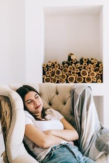 Jovem mulher caucasiana sentada em uma poltrona na sala de estar dormindo após um dia de trabalho duro, tirando uma soneca ou sonhando acordada