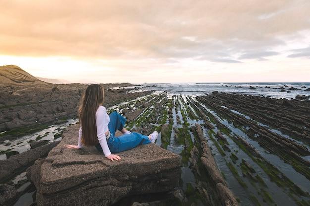Jovem mulher caucasiana, sentada em uma rocha na praia rochosa de sakoneta.