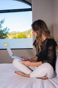 Jovem mulher caucasiana, sentada na cama em casa, assistindo canais da série em streaming