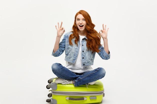Jovem mulher caucasiana sentada na mala e mostrando sinal de dedo bem