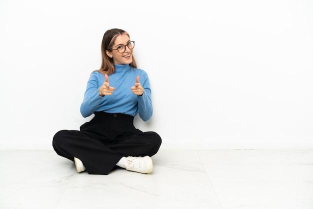 Jovem mulher caucasiana sentada no chão, apontando para a frente e sorrindo