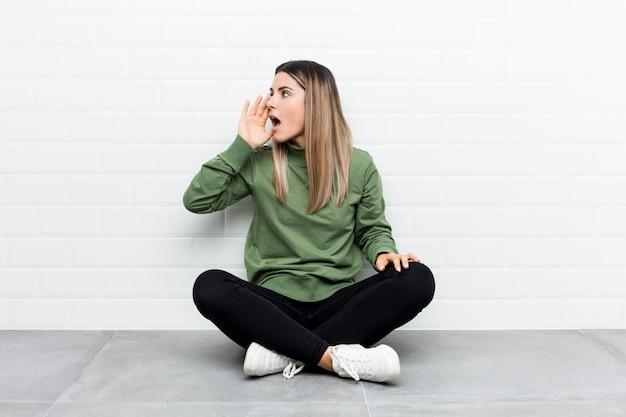 Jovem mulher caucasiana, sentada no chão, gritando e segurando a palma da mão perto da boca aberta.