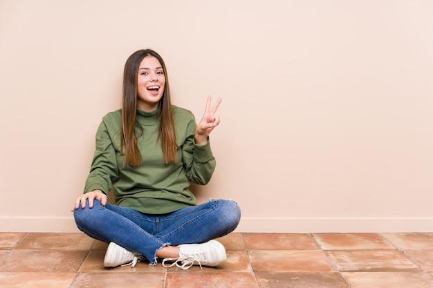 Jovem mulher caucasiana sentada no chão isolada alegre e despreocupada, mostrando um símbolo de paz com os dedos.