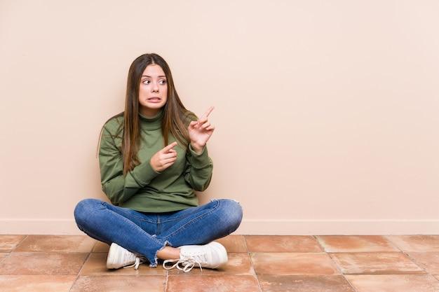 Jovem mulher caucasiana sentada no chão isolada chocada apontando com o dedo indicador para um espaço de cópia.