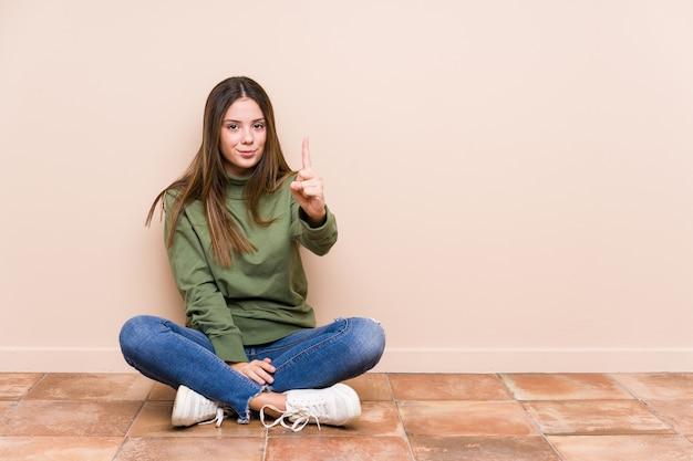 Jovem mulher caucasiana sentada no chão isolada mostrando o número um com o dedo.