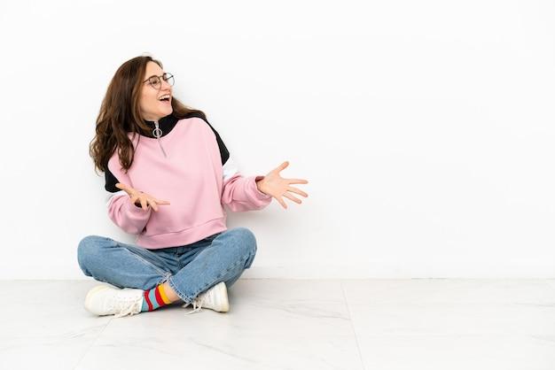 Jovem mulher caucasiana sentada no chão, isolada no fundo branco com expressão facial surpresa