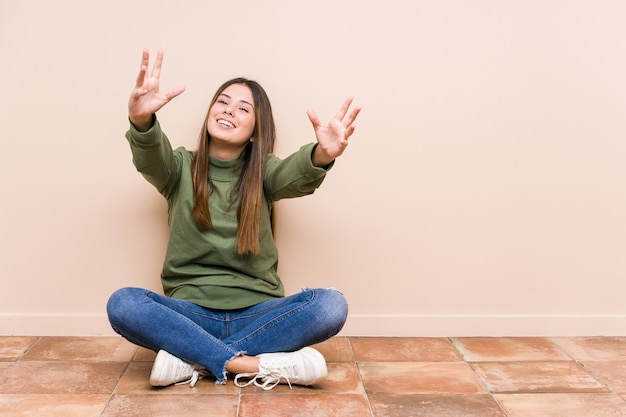 Jovem mulher caucasiana, sentada no chão isolada, sente-se confiante ao dar um abraço
