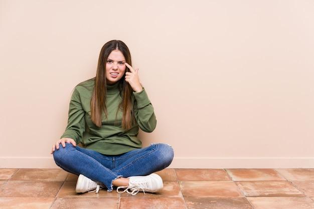 Jovem mulher caucasiana, sentada no chão isolado mostrando um gesto de decepção com o dedo indicador.