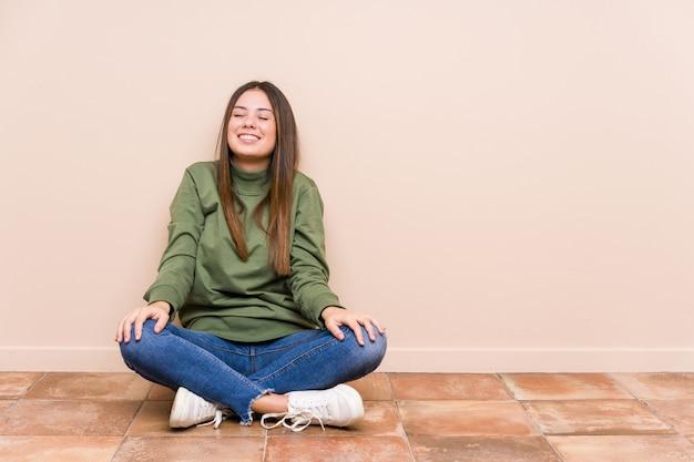 Jovem mulher caucasiana, sentada no chão isolado ri e fecha os olhos, sente-se relaxado e feliz.