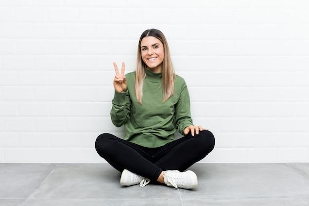Jovem mulher caucasiana, sentada no chão, mostrando o número dois com os dedos.