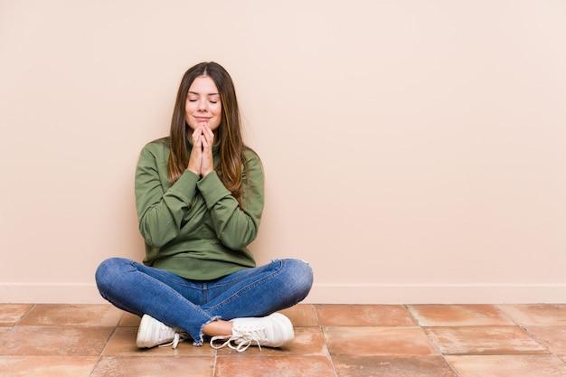 Jovem mulher caucasiana, sentada no chão, segurando as mãos em rezar perto da boca, sente-se confiante.