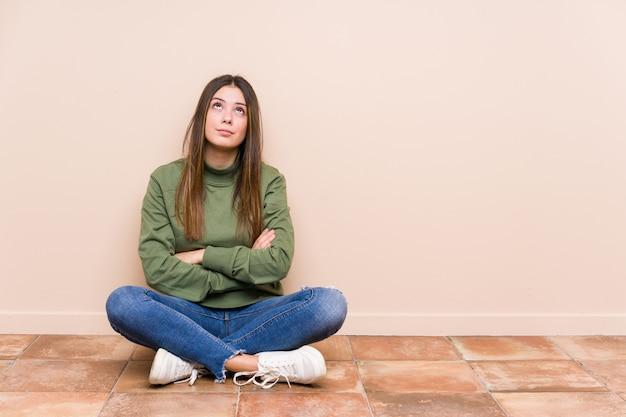 Jovem mulher caucasiana, sentada no chão